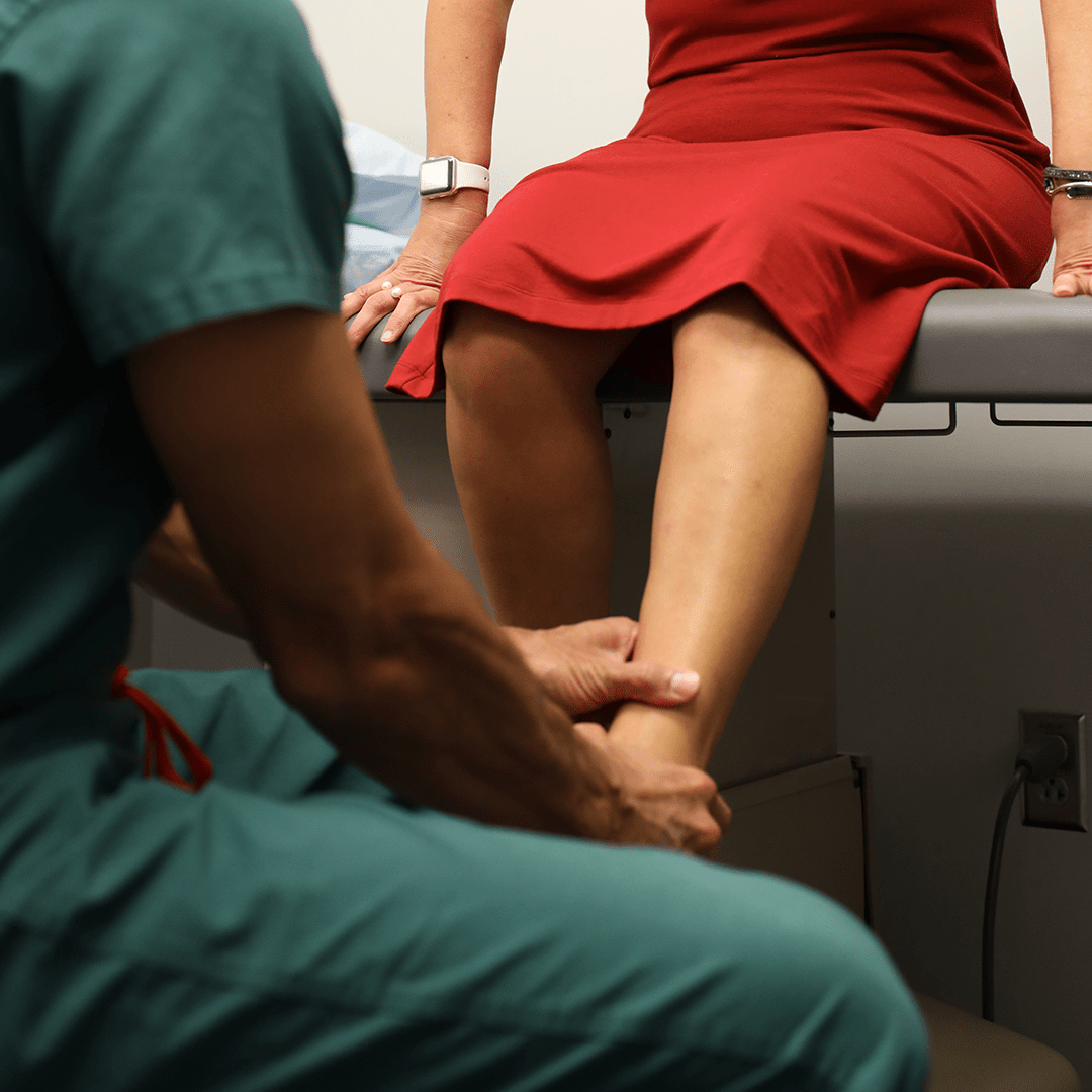 Therapist holding woman's ankle